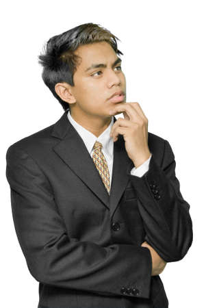 circumspect: Young dynamic Indian businessman, yuppie type, with hand on chin and looking up, and with a dreaming, pondering or worried expression on his face. Isolated over white.
