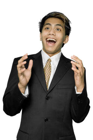 Young dynamic Indian businessman, yuppie type, smiling and looking up with a facial expression of a pleasant surprise and hands up like cheering. Isolated over white. Stock Photo - 4083842