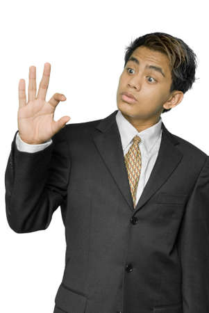 smallness: Size matters.Young dynamic Indian businessman, yuppie type, estimating size, bigness or smallness with his finger and thumb, with a pondering, amazed or worried expression on his face. Isolated over white.