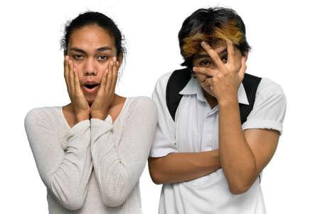 ショックを受けたアジア エモまたはサイド バイ サイドのカメラに直面していると全く嫌悪感や恐怖で自分の顔をカバーする髪を染めとパンクの十代の少年のカップル。白で隔離されました。 写真素材