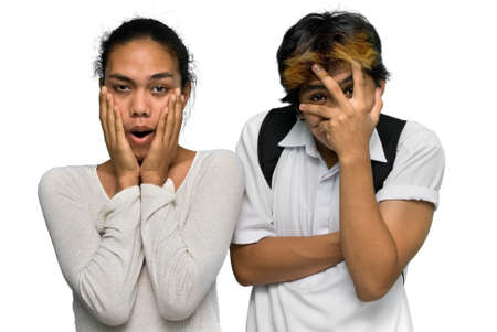 terrorized: Shocked Asian emo or punk teen boy couple with dyed hair facing camera side by side, and covering their faces in utter disgust or horror. Isolated over white.