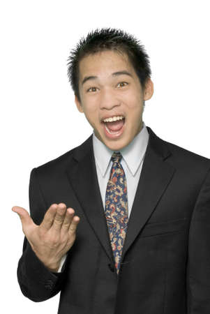 convincing: Close-up of young dynamic smiling and enthusiastic Asian businessman or salesman in suit making an explaining or convincing gesture with his hand. Isolated over white. Stock Photo
