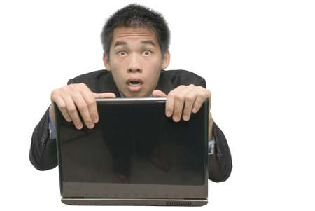 grasping: Young Asian businessman or salesman grasping and holding on to the screen, partially hiding behind a laptop PC, with a shocked, amazed, guilty and frightened look. Isolated over white.