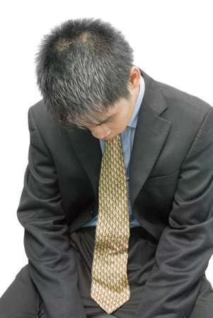 疲れている、過労、失望、落ち込んで若いアジア系のビジネスマン、セールスマンやフォーマルな服装とネクタイ、鳥の視点から床に向かって自分の頭で座っている金融株式トレーダー。白で隔離されました。 写真素材
