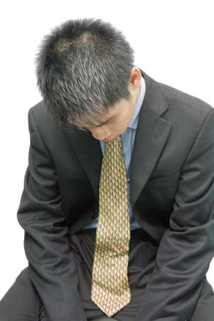 Tired, overworked, disappointed and depressed young Asian businessman, salesman or financial stock trader in formal attire and necktie, sitting with his head towards the floor, from a birds perspective. Isolated over white. photo