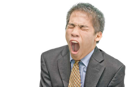 Portrait of intensely yawning tired and overworked young Asian businessman or salesman in formal attire, frowning with wide open mouth and eyes closed. Isolated over white with copyspace.