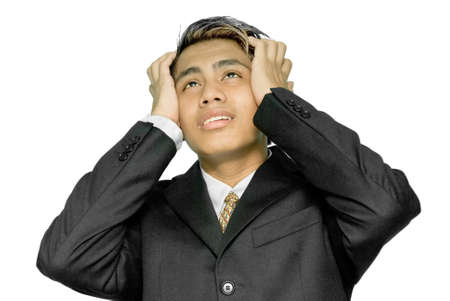 Young Indian businessman, yuppie type, holding his head in his hands looking up in a stressed gesture and with an expression of despair on his face. Isolated over white.