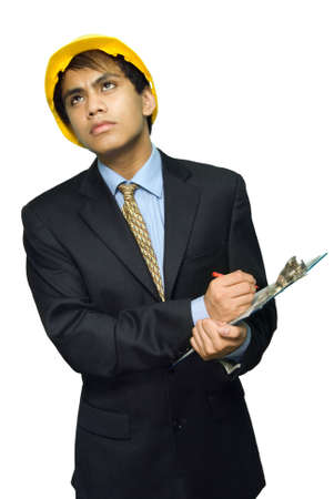 Young Indian engineer or architect in business suit and with yellow hardhat frowning and peering worriedly while taking notes on a notepad or clipboard. Isolated over white.