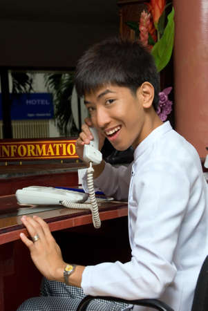 Asian smiling and welcoming hotel receptionist boy holding telephone hook or calling sitting at the desk of a hotel lobby with an information sign. photo