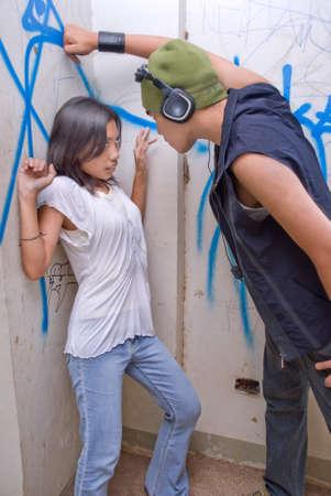 若いタフなアジア男性ラッパー ヘッドセットと落書きの壁の都市環境で追い詰められたとおびえた女の子威圧的なキャップを持つ。 写真素材
