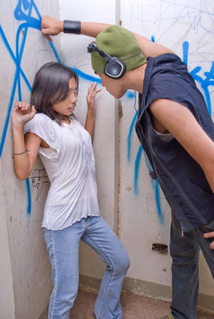 harassing: Young tough Asian male rapper with headset and cap intimidating a cornered and frightened girl in an urban environment with graffiti on the wall. Stock Photo