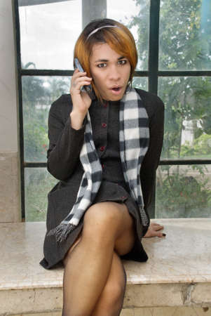 shemale: Girl in formal attire wearing net stockings and high heels calling by cellphone in a dirty neglected urban setting with graffiti. Caveat: (she)male impersonator. Stock Photo