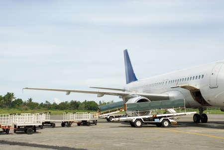 商業定期旅客機または飛行機開いた貨物湾の側で荷物カートと熱帯空港の駐機場に停めた。
