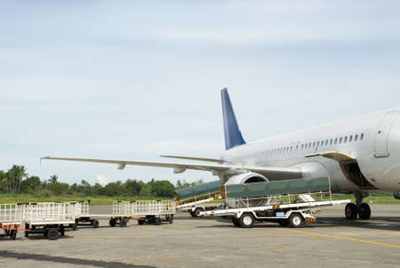 airliner: Commercial airliner or airplane with open cargo bays parked on the tarmac of a tropical airport with luggage carts at the side. Stock Photo