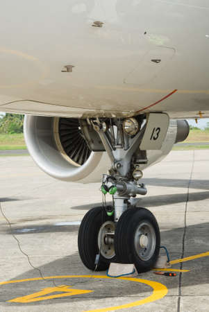 Detail of the nose wheel of the landing gear of a commercial airliner or airplane parked on the tarmac of an airport. photo