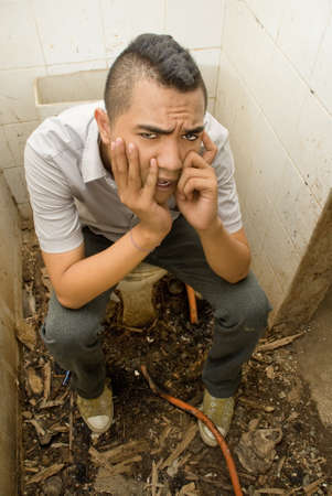 Desperate young male Asian emo punker hanging wasted and with a hopeless expression in a vandalized urban small washroom or lavatory, floor scattered with debris. Concept or urban decay and drug abuse. Caveat: scene is staged, model is an actor. photo