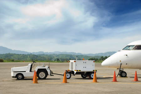 electricity generator: Transportable electricity generator (auxiliary power unit, APU) with tractor in front of a parked airplane nose on the tarmac, while pilots are preparing their flight.
