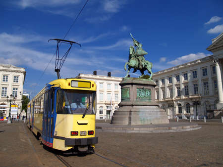 The Brussels, Belgium Royal Square with the statue of Godfrey of Bouillon and tram, and the buildings of the Belgian federal Supreme Court in the background.
