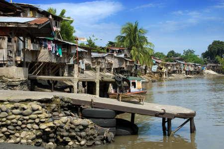 アジアのスラム街、貧しい住宅物干し、ヤシの木と熱帯の泥だらけの川の銀行に桟橋が付く。