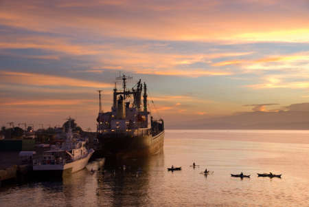 beggars: Flamboyant colorful early exotic sunrise in the dawn over a tropical port with a cargo ship and small beggars� and fishermens boats in the foreground. Stock Photo