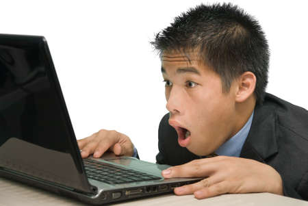 awe: Close-up of amazed young Asian yuppie businessman, staring in awe at his laptop screen. Isolated over white.