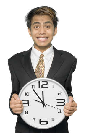 pressured: Young Indian businessman, yuppie type, stressed with a desperate and pressured grin on his face, holding a clock pointing five to twelve symbolizing a deadline he has to meet. Isolated over white.
