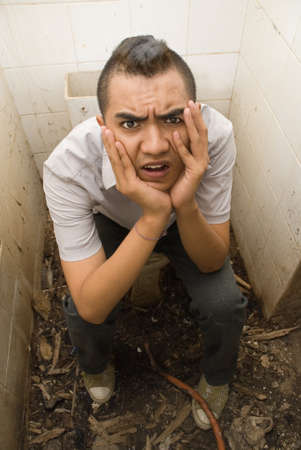wasted: Desperate young male Asian emo punker sitting wasted and with a hopeless expression in a vandalized urban small washroom or lavatory, floor scattered with debris. Concept or urban decay and drug abuse. Caveat: scene is staged, model is an actor.