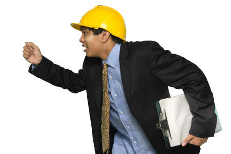 Rushing and running young Indian engineer or architect in suit with yellow hardhat and clipboard in one hand, in profile, upper body. Isolated over white. photo