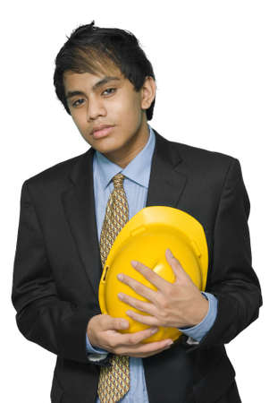 humbled: Mourning or pensive young Indian engineer or architect in business suit with yellow hardhat pressed in his chest. Isolated over white.