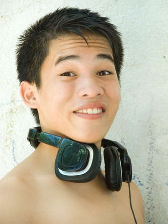 elated: Portrait of surprised and smiling Asian male teenager, eyebrows lifted, with headset outside against a stucco wall. Stock Photo