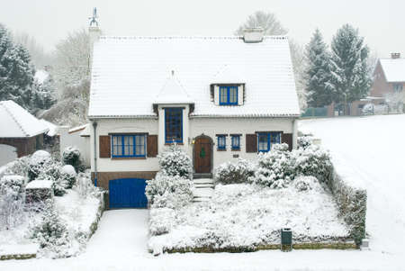 Residential suburban European middle class stone house in winter, covered with snow.