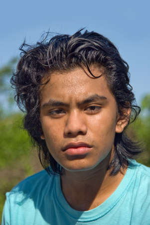 Closeup portrait of sweaty tired and sweaty Indian teenage jogger with curly black hair outdoors. photo