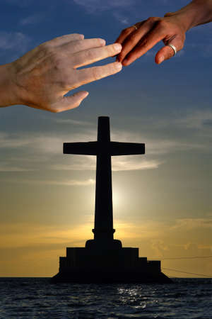 Large concrete cross silhouette over a marine sunset with a Caucasian and a black hand touching on top in unity.