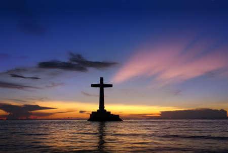 Kleurrijke tropische zee zonsondergang met een grote betonnen kruis silhouet over Verzonken Cemetery, Camiguin, Filipijnen.
