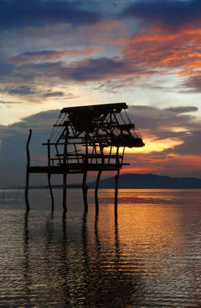 Flamboyant, exotic, tropical and colorful sunset over sea and mountains with a pole house skeleton silhouette in front in the water. Bohol, Philippines. Zdjęcie Seryjne