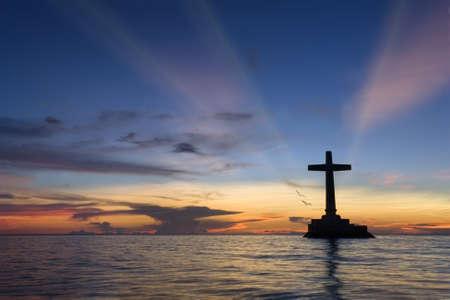 サンケン墓地、カミギン島、フィリピンに大規模なコンクリート クロス シルエットと色鮮やかな熱帯海洋日没。破壊古都コッタ馬頭、1871年火山噴火の犠牲者の記念。