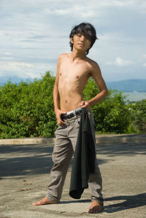 mocking: Teenage Asian skinny shirtless boy striking a fashion pose in a tropical landscape with bay in the background. Stock Photo