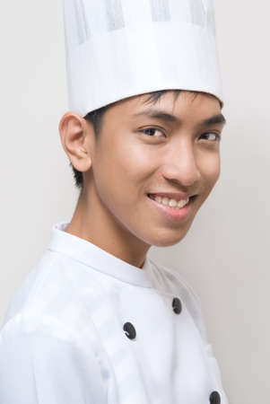 Closeup portrait of a young smiling oriental Chinese cook or chef with cook's hat and in white cook's clothes. Zdjęcie Seryjne