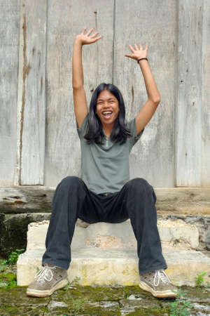 victorious: Asian long haired teenager cheering and shouting happily like a winner with arms up, sitting outdoors against a worn wooden wall.
