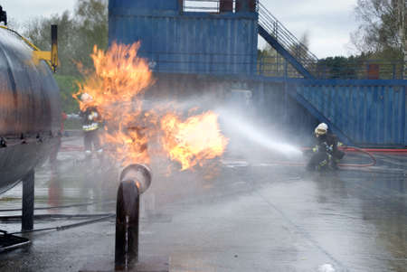 brigade: Firefighters in protective uniform and helmet extinguishing pipeline and fuel tank fire with a hose and water jet in an industrial location.