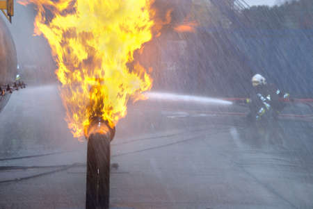Firefighters in protective uniform and helmet extinguishing pipeline and fuel tank fire with a hose and water jet in an industrial location.