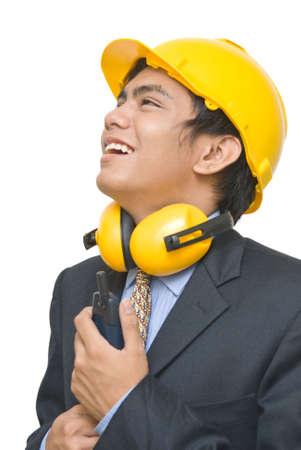 Portrait of smiling and happy Indian foreman, contractor or architect in suit, looking up with hardhat, ear protector holding a walkie-talkie. photo