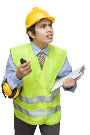 Young Indian foreman or contractor in safety gear looking up with a worried facial expression. Isolated over white.