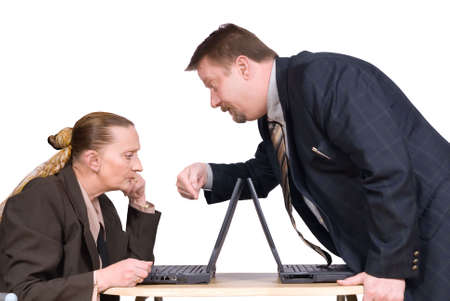 instructing: Dominant corporate male business boss or manager standing, bending over, pointing and instructing a sitting attentive female co-worker on her laptop screen in the office. Isolated over white. Stock Photo