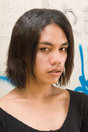 Portrait of an effeminate androgynous long haired emo or punk South East Asian teenager with a low neckline dress on the background of a graffiti wall.