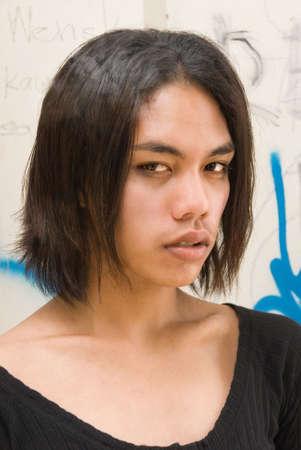 south east asian: Retrato de un afeminado andr�gino de pelo largo emo punk o del sudeste asi�tico adolescente con un vestido escote bajo en el fondo de una pared de graffiti. Foto de archivo