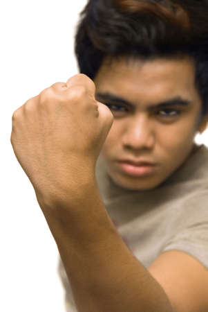 Masculine clenched closed fist close-up in an aggressive macho gesture, in focus with a blurred determined face in the background. Isolated over white. photo