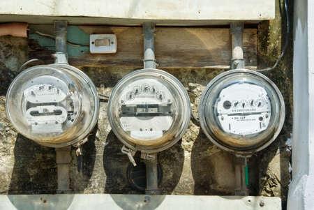 3 錆びた古い機械の住宅の電気メートルの行はめちゃめちゃ管と配線の貧しい人々 の壁屋外にマウントされています。