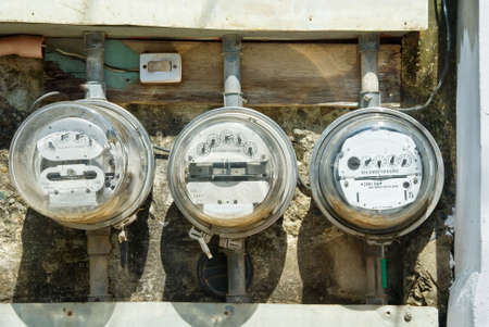 electric utility: Three rusted old mechanical residential electricity meters in a row mounted on a poor wall outdoors with messed tubes and wiring. Stock Photo