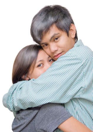 Asian and Indian mixed teenage couple in a tight, protective and tender embrace. Girl hiding in boy�s arms. Isolated over white. photo